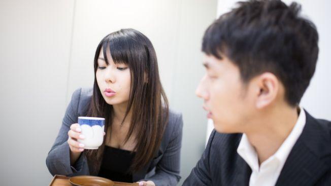 Seorang karyawan meniup minuman di depan karyawan lainnya (soranews24)