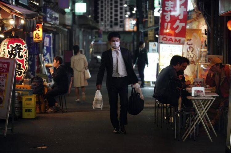 Seorang pria melewati jalan di Tokyo pada 28 April 2020. Ia terlihat mengenakan masker untuk mencegah penyebaran virus, namun terlihat di belakangnya masih ada warga yang berkumpul dan tidak memakai masker. (japantoday.com)