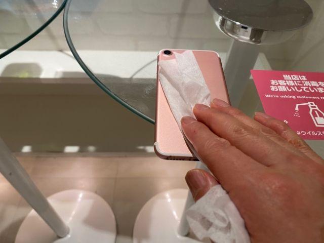 Mengelap smartphone dengan desinfektan (soranews24.com)